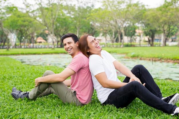 웃으면 서 공원에서 잔디에 앉아 두 남자