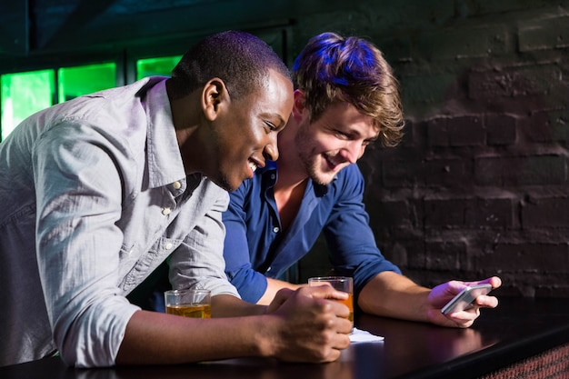 Two men looking at mobile phone and smiling while having whiskey at bar counter in bar