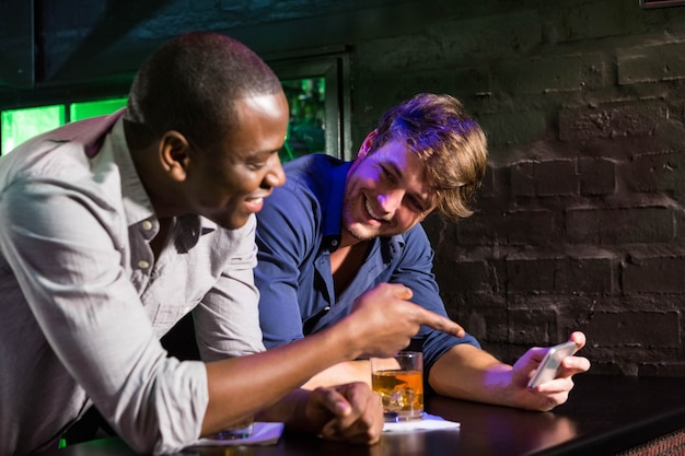 Two men looking at mobile phone and talking while having whiskey at bar counter in bar