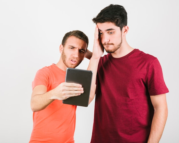 Two men looking puzzled at tablet screen