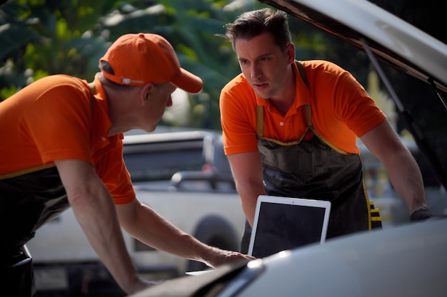 Two men, a mechanic, are using a laptop to check and condition their engines.