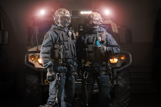 Two men in military uniforms stand in a hangar with a truck