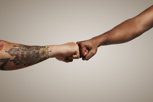 Two men one light skinned with tattoos and another dark skinned do a fist bump on white wall close up