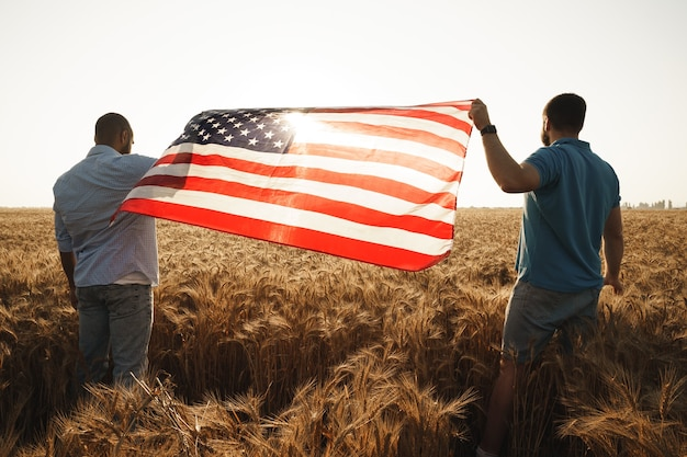 Two men patriots holding us flag above wheat field