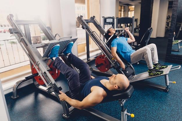 Two men perform physical exercise on leg strength