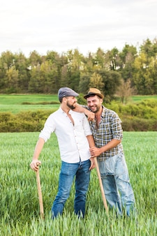 Two men in plaid shirt standing in oat field with forest