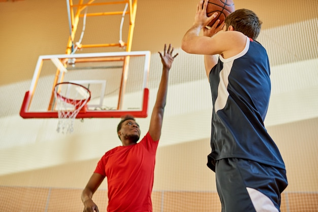 Two men playing basketball in gym