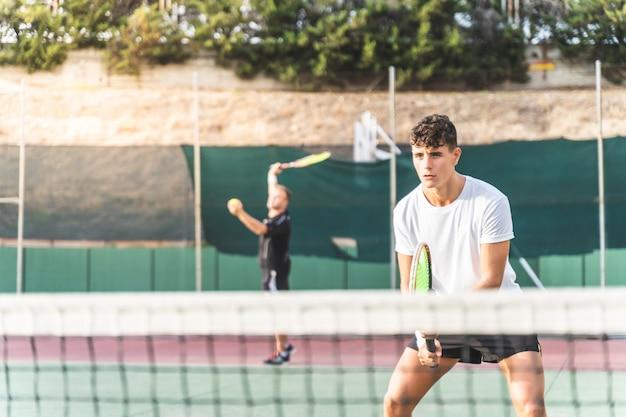 야외에서 팀으로 테니스를하는 두 남자.