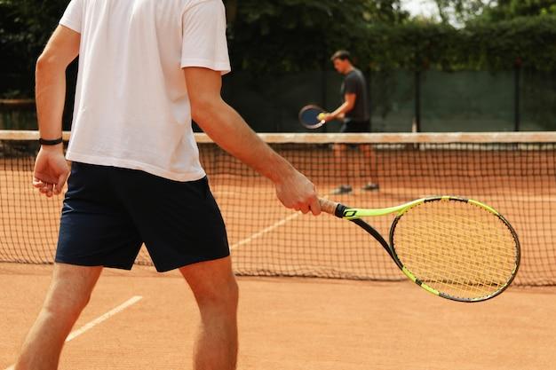 Двое мужчин играют в теннис на грунтовом корте