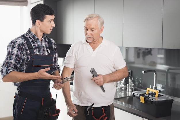 Two men of plumbers stand in kitchen and choose tool.