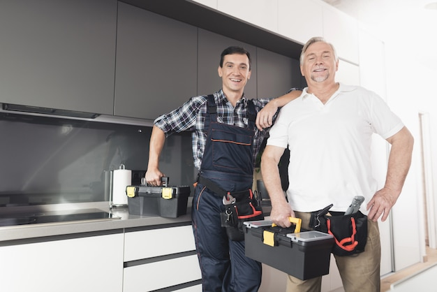 Two men of plumbers stand in the kitchen.