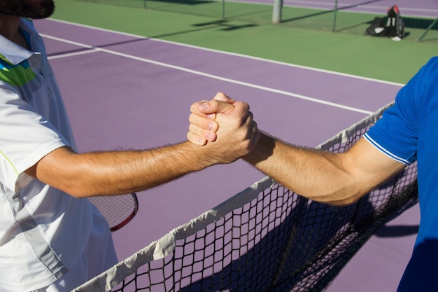 Two men, professional tennis players shake hands before and after the tennis match