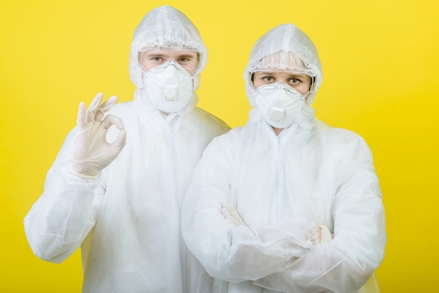 Two men in protective suit respirator masks isolated