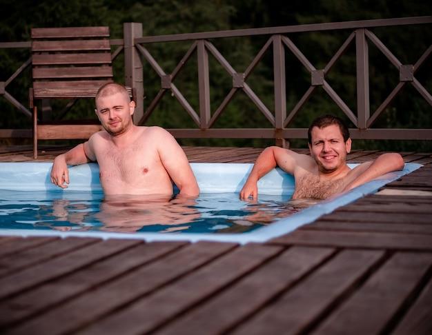 二人の男が森を背景にプールでリラックス