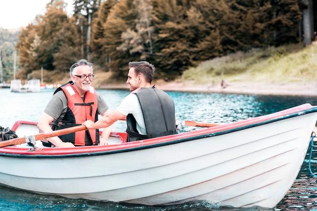 Двое мужчин гребут на лодке по спокойному озеру