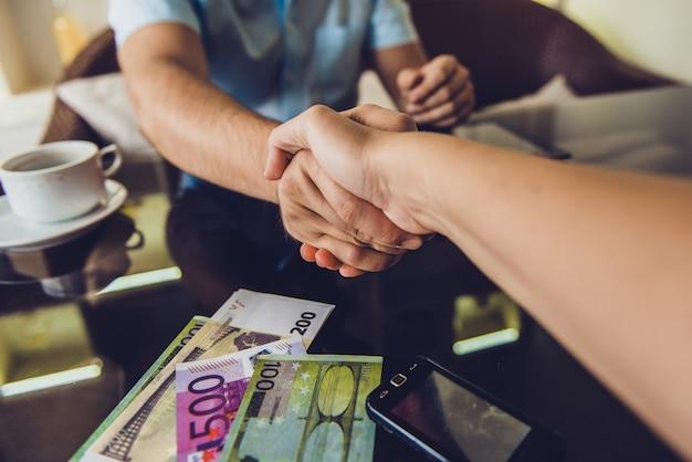 カフェで握手する2人の男性。