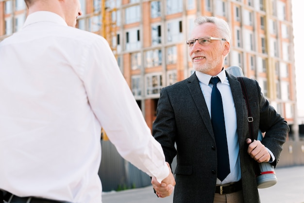 Two men shaking hands outdoors