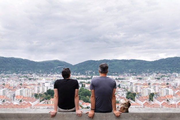 Two men sit on the edge of a tall building and look into the distance to the mountains.