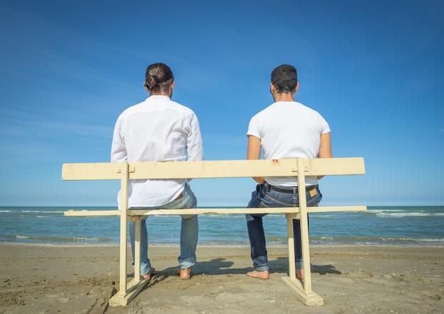 Двое мужчин сидят на скамейке и смотрят на море.
