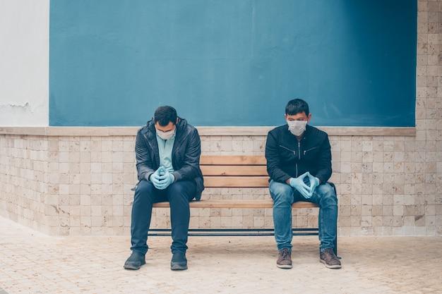 日中庭で心配してベンチに座っている2人の男性。