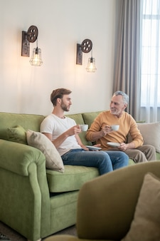 Two men sitting on the sofa and having tea