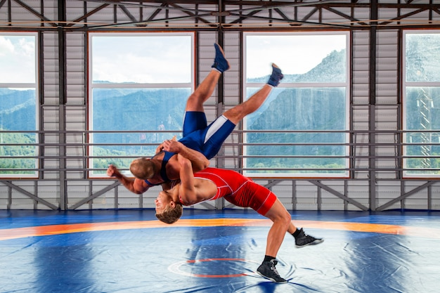 Two men in sports wrestling tights and wrestling during a traditional greco-roman wrestling in fight on a wrestling mat
