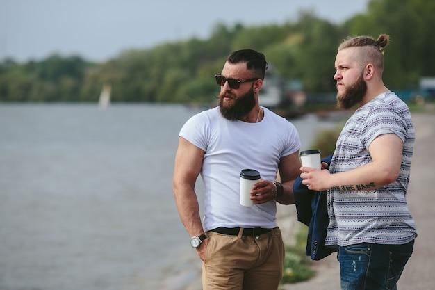 두 남자가 서서 커피를 마신다