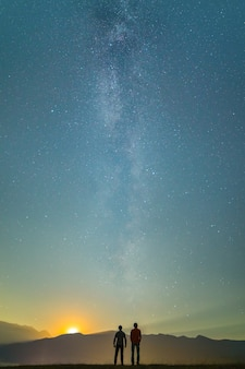 The two men stand on the background of the milky way. night time