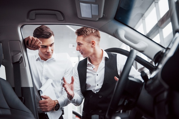 두 남자가 쇼룸에서 자동차를 향해 서 있습니다. 고객에게 자동차를 판매하는 소송에서 영업 관리자의 클로즈업. 판매자는 고객에게 열쇠를 제공합니다.