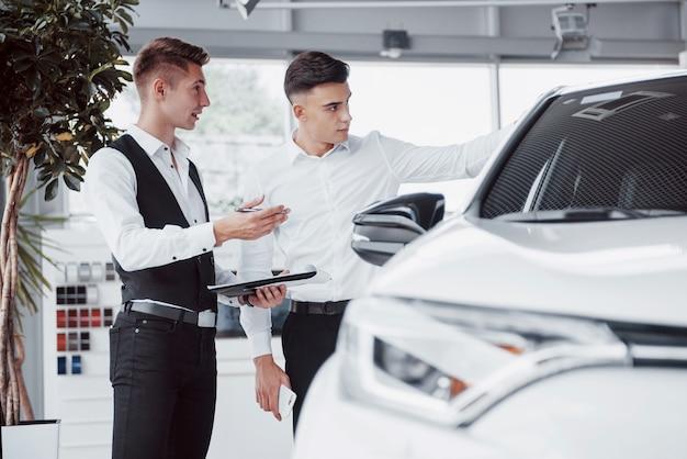 2人の男性がショールームに車に向かって立っています。顧客に車を販売するスーツを着たセールスマネージャーのクローズアップ。売り手は顧客に鍵を渡します。