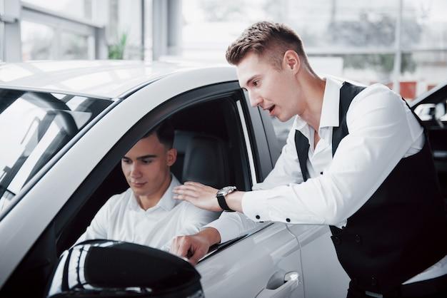 Due uomini stanno nello showroom contro le macchine. primo piano di un responsabile vendite in una tuta che vende un'auto a un cliente. il venditore fornisce la chiave al cliente.