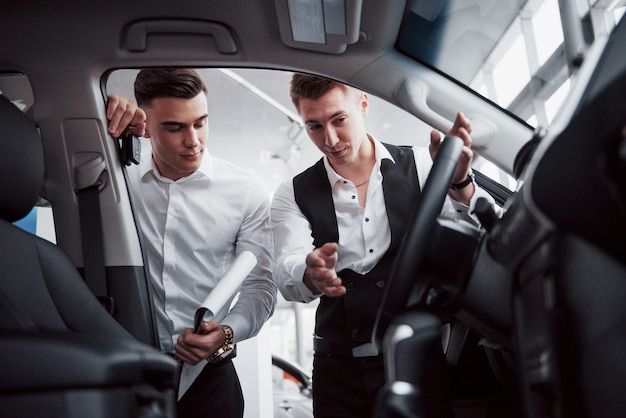 Two men stand in the showroom against cars. close-up of a sales manager in a suit that sells a car to a customer. the seller gives the key to the customer.