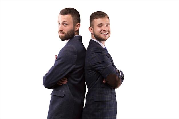 Двое мужчин стоят спиной к спине и поддерживают друг друга
