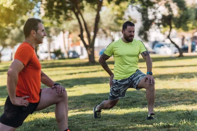Двое мужчин растягиваются во время шпагата в парке