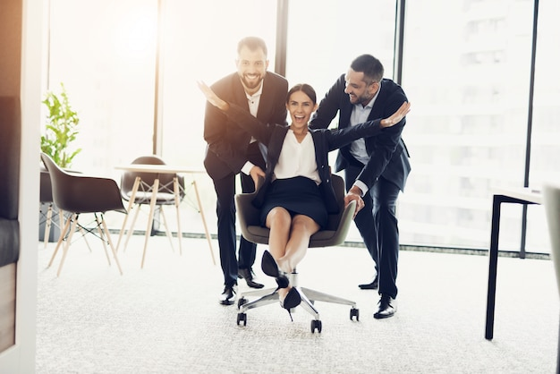 Two men in strict business suits roll their office employee.
