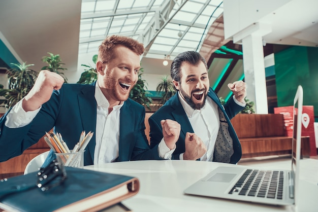 Two men in suits celebrating looking on laptop in office.