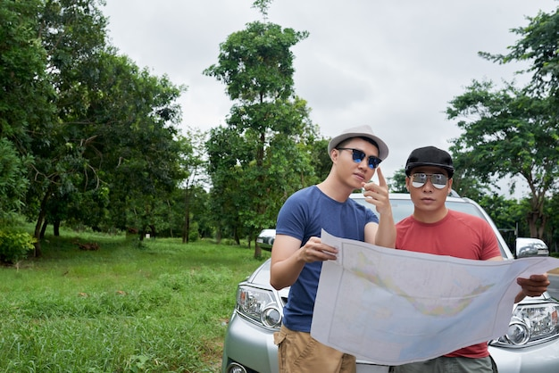 Two men in sunglasses standing by car, holding large map and pointing