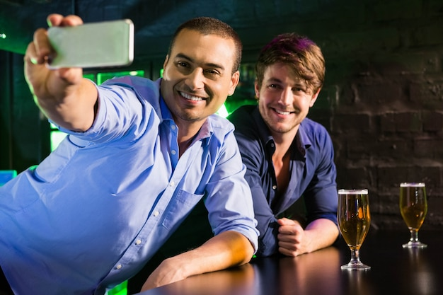 Two men taking a selfie on phone while having beer at bar counter in bar