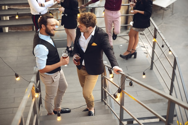 Two men talking, celebrating, look happy, have corporate party at office or bar