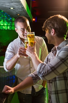 Two men toasting with glass of beer at bar counter in bar