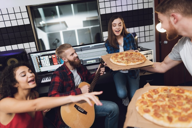 Two men and two women in recording studio are eating pizza.