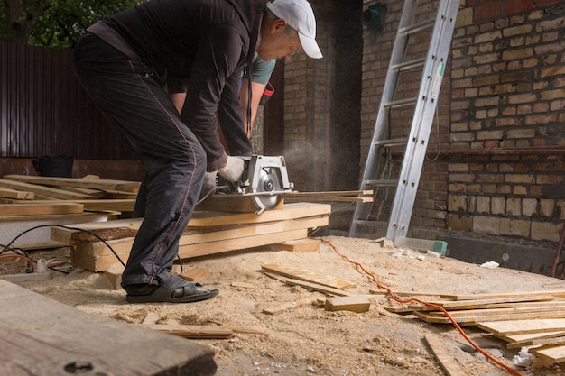 가정용 전동 톱을 사용하여 주택 건설을 위한 나무 판자를 절단하는 두 남자 바닥에 톱밥 더미를 남기고