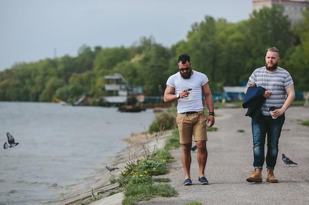 두 남자가 걷고 커피를 마신다.