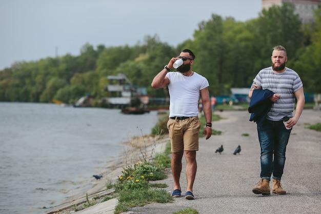 Due uomini camminano e bevono caffè
