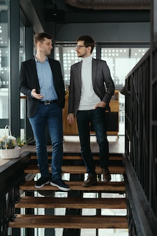 Two men walking down stairs chatting indoors