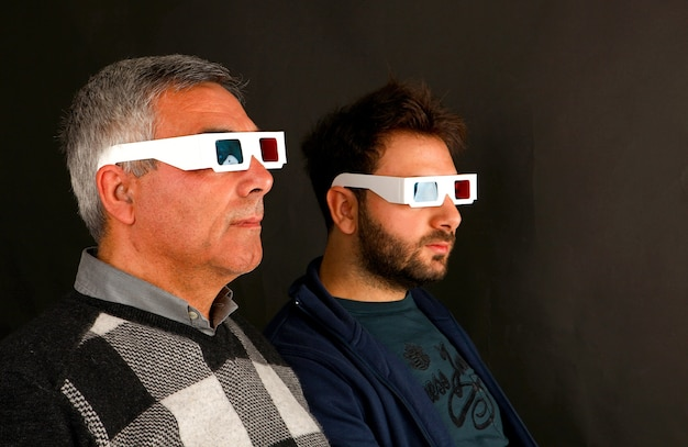 Two men wearing 3d glasses on black wall