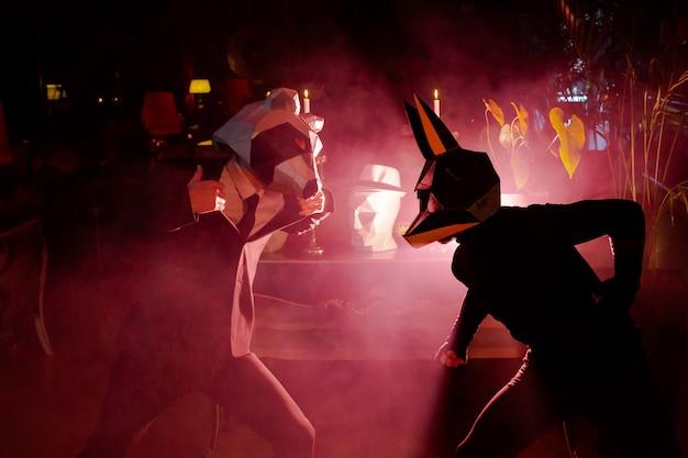 赤いライトが付いているクラブのパーティーで動物のマスクを着ている2人の男性