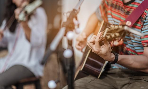 2人の男性が音楽を演奏していました。1人はギターを演奏し、もう1人は音楽のステージでバイオリンを演奏していました。
