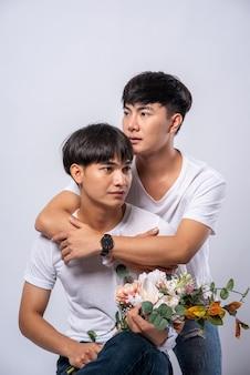 お互いを愛する二人の男が後ろから抱擁します。