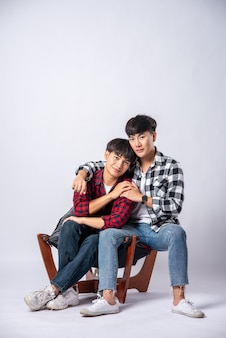 Two men who love each other hug and sit on a chair.